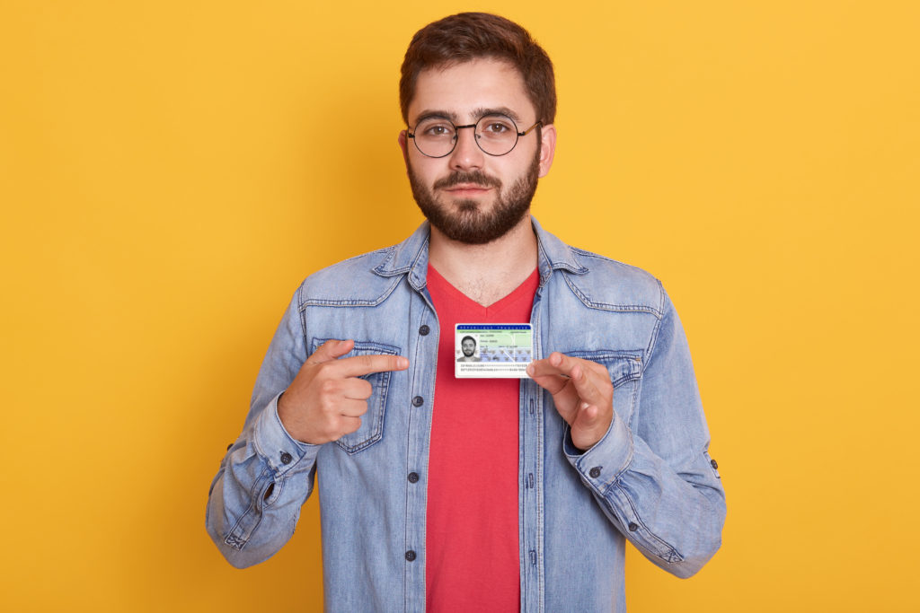 Portrait of confident bearded man pointing with his index finger to credit card, male looking to camera, paying with card for purchase, wearing denim jacket and red casual shirt.